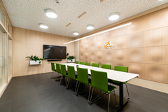 Height adjustable meeting table, monoblock visitor chairs, perforated 3D acoustic wall panels, bended plywood LED ceiling lamp